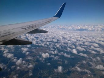 View over airplane wing through the clouds to the land far below.