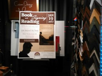 Book signing and reading poster in window of art gallery and frame shop