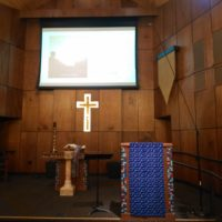 Pulpit with Ray's PowerPoint presentation projected on the wall behind it.